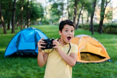 Surprised boy holding digital camera near camps in park stock vector