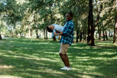 happy african american father holding in arms cute son in park
