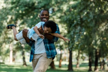 smiling african american father holding n arms cute son in green park