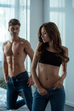 selective focus of attractive girl undressing in bedroom near handsome man