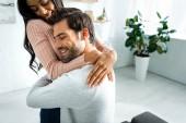 afro-amerikai nő és csinos férfi mosolygott és átölelve a lakásban