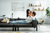 african american woman and handsome man smiling and sitting on sofa in apartment