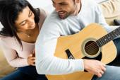 usmívající se Africká Američanka na muže s akustickou kytarou
