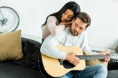 afro-amerikai nő ölelgetés jóképű férfi akusztikus gitár