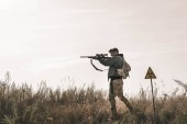 Fotografia bello uomo tenendo pistola vicino simbolo tossico in campo, concetto post apocalittico