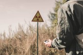 oříznutý pohled na člověka držícího radiometr poblíž toxického symbolu, post apokalyptický koncept