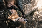 Photo selective focus of kid in gas mask holding radiometer, post apocalyptic concept