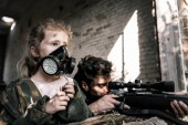 Photo selective focus of kid in gas mask near man with gun, post apocalyptic concept