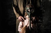 Photo cropped view of man standing near kid in gas mask, post apocalyptic concept