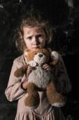 frustrované dítě držící plyšového medvídka ve špinavém pokoji, post apokalyptický koncept
