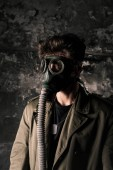 Photo man in gas mask standing near weathered wall in old room, post apocalyptic concept