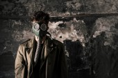 Photo man in gas mask standing near weathered wall, post apocalyptic concept