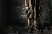 Photo cropped view of man holding gas mask while standing near old wall in abandoned room, post apocalyptic concept