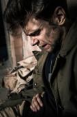 pohledný muž se špinavou tváří trpící bolestí, post apokalyptický koncept