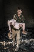 rozrušený muž drží v náručí dítě s medvídkem poblíž opuštěné budovy, post apokalyptický koncept