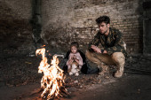 selective focus of man and child sitting near bonfire, post apocalyptic concept
