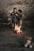 selective focus of man wearing jacket on child near bonfire, post apocalyptic concept