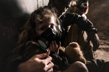 selective focus of man hugging kid in gas mask with teddy bear, post apocalyptic concept