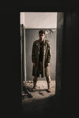 handsome man standing in old room in chernobyl, post apocalyptic concept