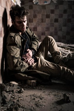 man with dirty face suffering pain while sitting on floor, post apocalyptic concept