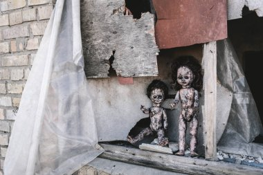 scary and burnt baby dolls near rusty window, post apocalyptic concept