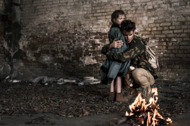 handsome man hugging child near burning bonfire, post apocalyptic concept