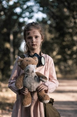 dirty kid holding dirty soft toy near trees in chernobyl, post apocalyptic concept