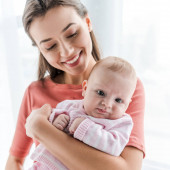 smiling mother holding in arms adorable infant daughter at home