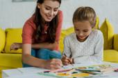 Fotografie selektivní zaměření šťastné hlídání sedící na žluté pohovce a kreslení s dítětem