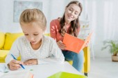 selective focus of cute child studying near attractive babysitter at home