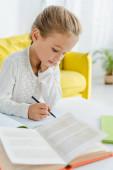 selektivní zaměření roztomilé dítě studuje doma