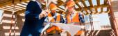 panoramic shot of businessman near builders holding blueprint