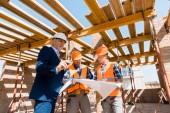 mature businessman near builders in helmets holding blueprint