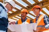 low angle view of builders near mature businessman in helmet with blueprint