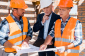 mature constructor pointing with finger at blueprint near businessman