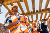 Fotografie low angle view of handsome bearded builder holding measuring tape