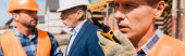panoramic shot of builder holding walkie talkie while talking near coworker and businessman