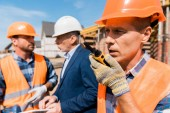 selective focus of builder holding walkie talkie while talking near coworker and businessman