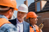 selective focus of constructor near bearded businessman and coworker in helmets