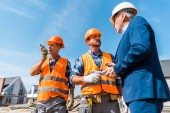 builder holding walkie talkie near coworker and businessman with digital tablet