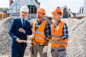 Fotografie constructors in helmets standing near businessman with digital tablet