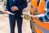 cropped view of constructor holding walkie talkie near coworker and businessman with digital tablet