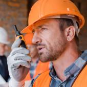 Fotografie selective focus of handsome builder talking while holding walkie talkie