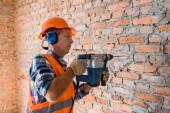 mature builder in helmet using hammer drill near brick wall