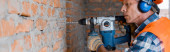 Fotografie panoramic shot of mature builder using hammer drill near brick wall