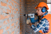 Fotografie mature builder using hammer drill near brick wall