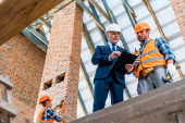 low angle view of bearded businessman holding clipboard near builders