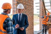 Fotografie bearded businessman in helmet holding clipboard near constructors