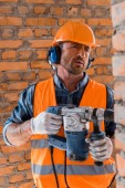 selective focus of handsome and bearded constructor holding hammer drill near brick wall