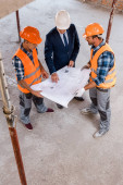 Fotografie overhead view of constructors and businessman holding blueprint